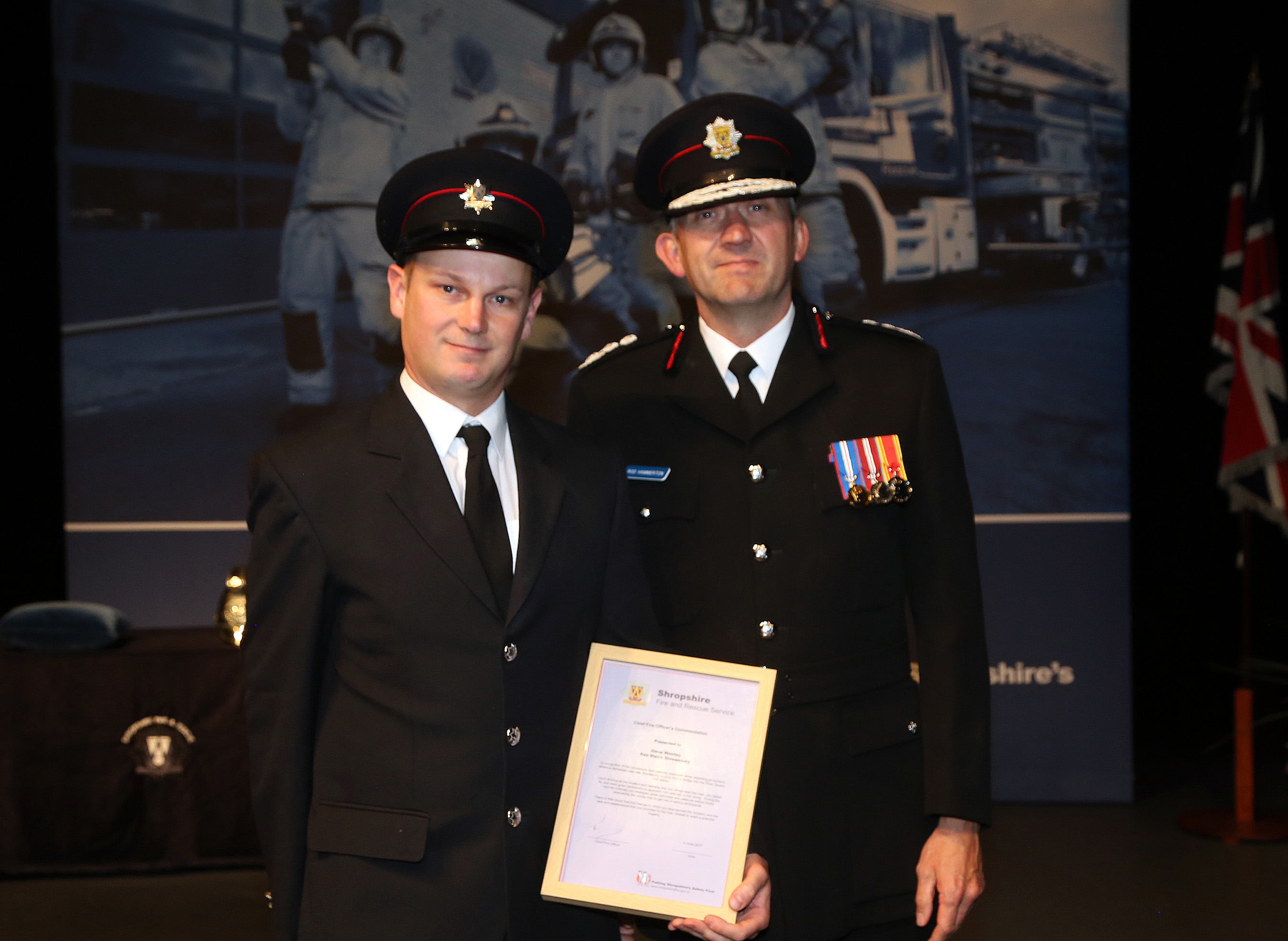 "Shrewsbury firefighter Steve Westley receives the Chief Fire Officer's Commendation from Rod Hammerton for his ""cool-headed"" actions in talking down a young man who was preparing to jump from a bridge into the River Severn."