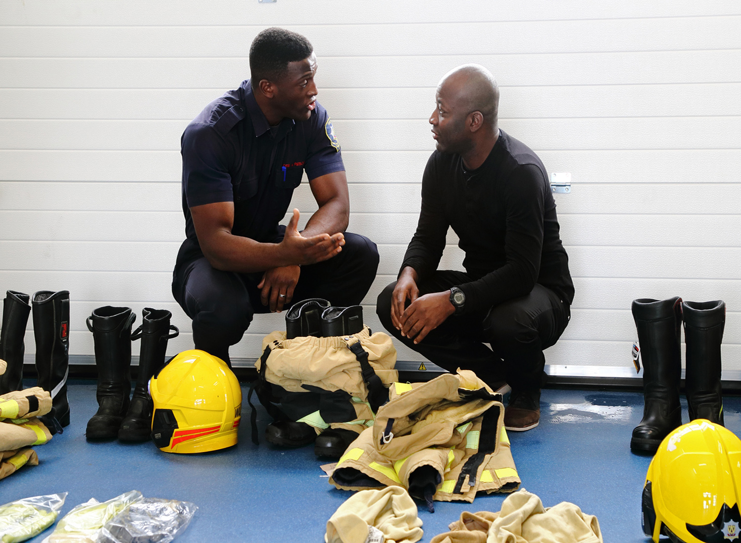 Firefighter Luke Grant talks about fire kit to Army reservist Fitzroy Lindsay