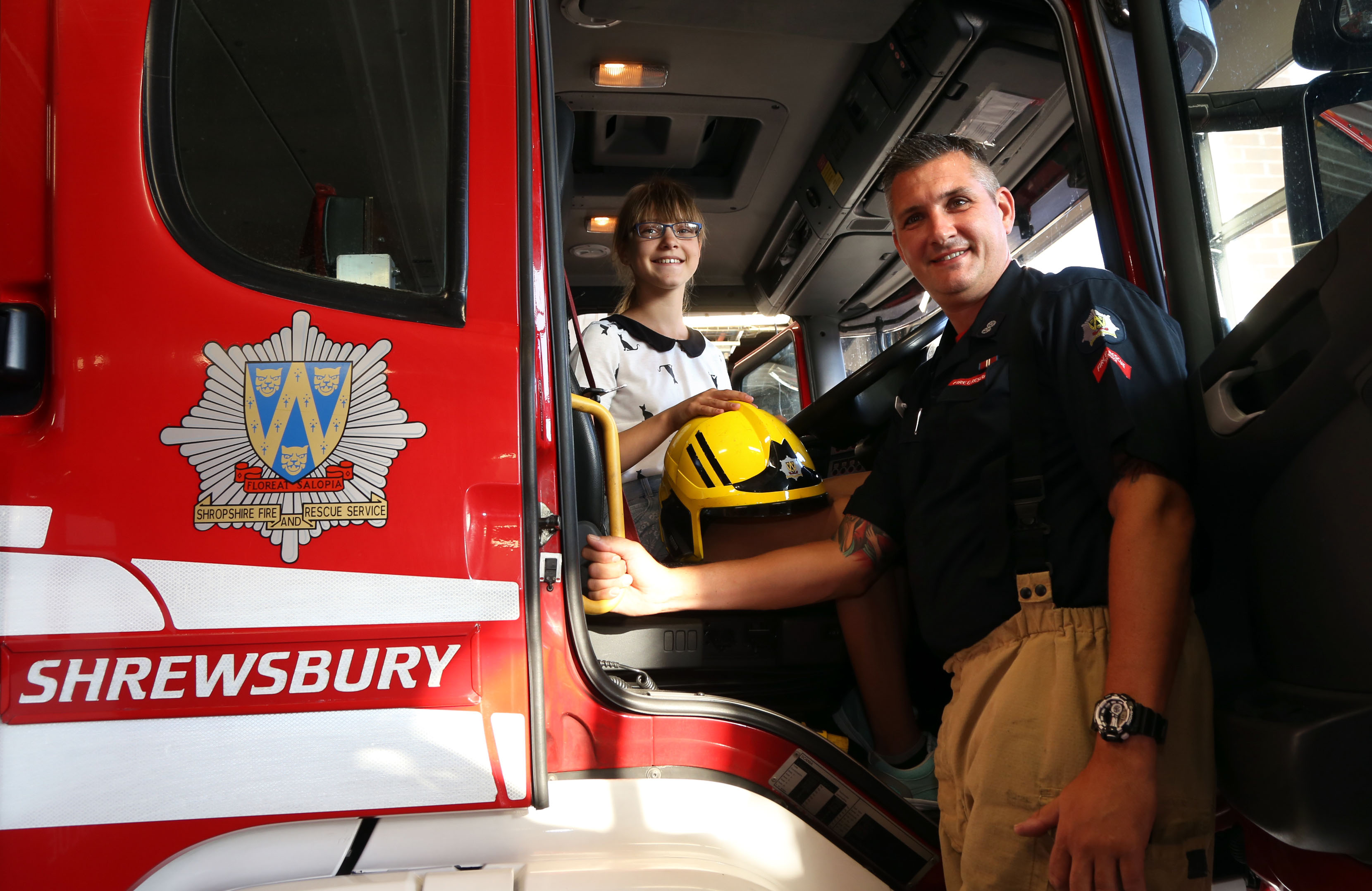 Blue Watch Shrewsbury Watch Manager Paul Gray with Vlada Shatilo (12) as she enjoys the view from the driver's seat