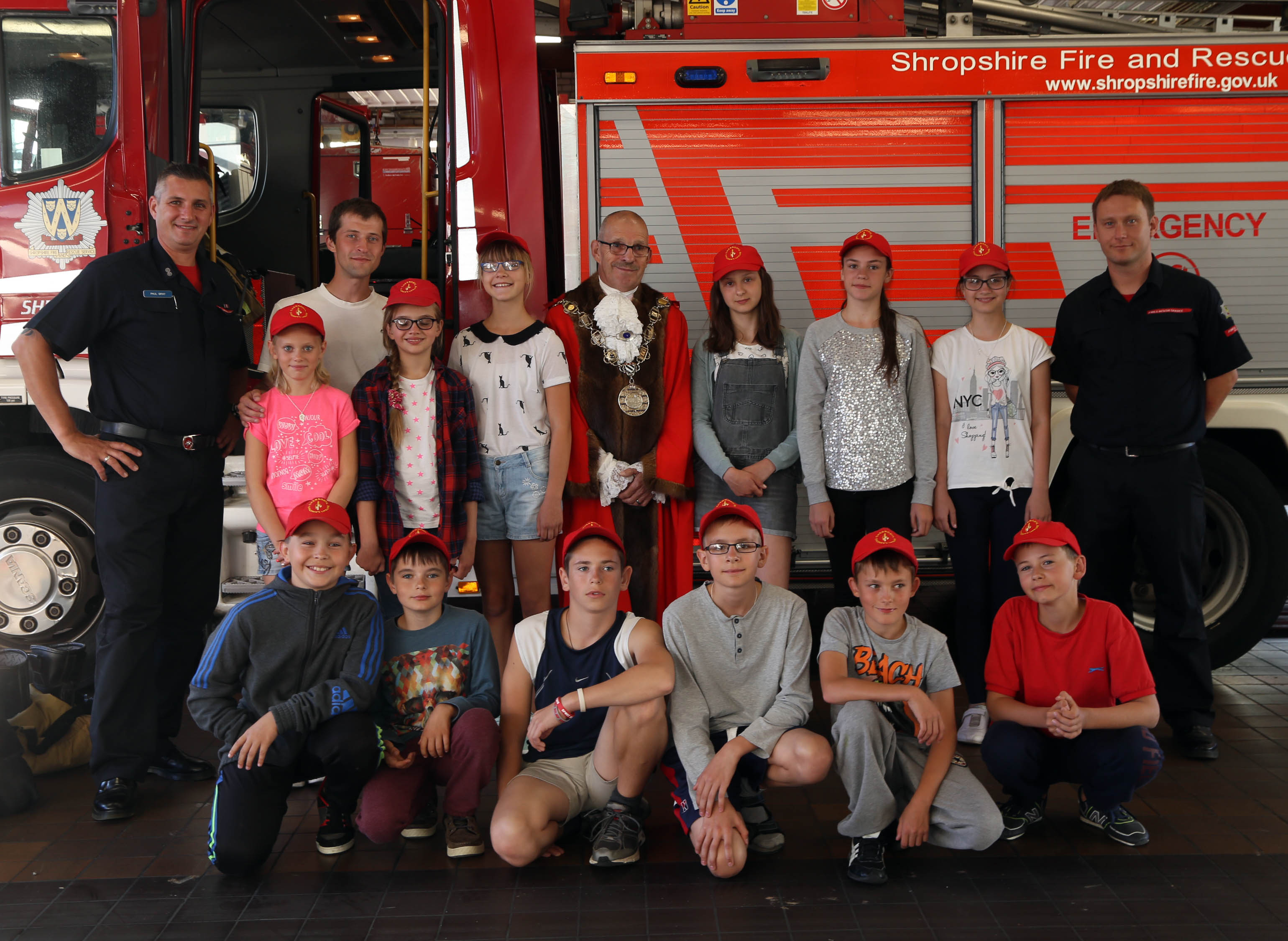 A formal line up in front of a Shropshire Fire and Rescue Service appliance as a memory of the trip to Shrewsbury Fire Station by children from Chernobyl