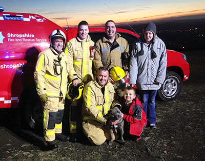 Firefighters and family pose for a group photo in front of a fire service pickup at sunset