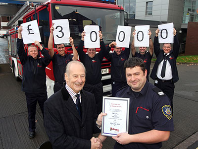Row of firefighters holding up cards which together spell out £30000
