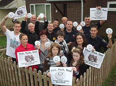 Friends, family, and firefighters pose with posters and smoke alarms in front of the house