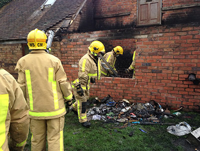 Firefighters examine fire damage