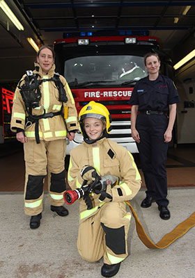 Two visitors and one firefighter pose in front of a fire appliance, the visitors are dressed in full protective kit