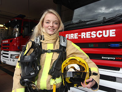 Laura Davies poses next to appliance in full protective kit holding a helmet under her arm