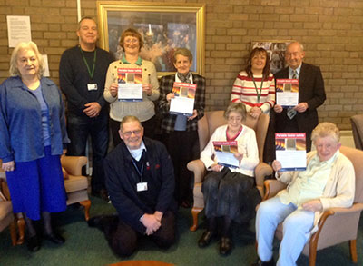 Group photo with several people including residents holding fire safety leaflets