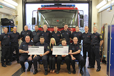 Group shot in appliance bay in front of fire appliance