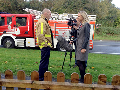 Firefighter and reporter pictured in front of a fire appliance with camera man filming