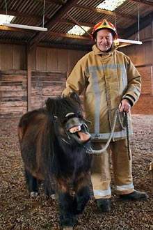 Stuart West holding a Shetland pony which is pulling a face at the camera