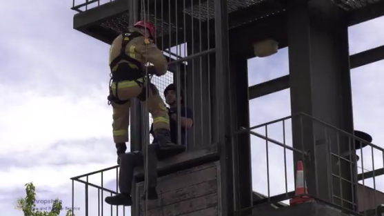 Firefighter Matt Stenton rescues a colleague from a tower in a demonstration or rope skills at Telford fire station's open day