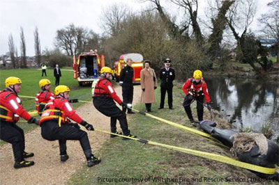 Firefighters drag training mannequin horse from a river
