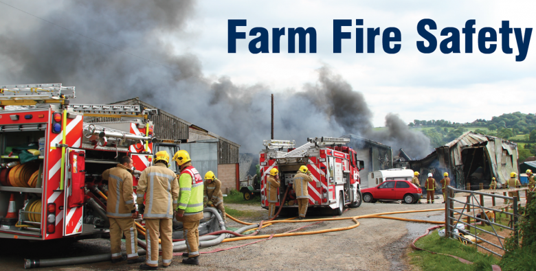 A country lane with fire engines parked and fire and smoke from a barn on fire beyond