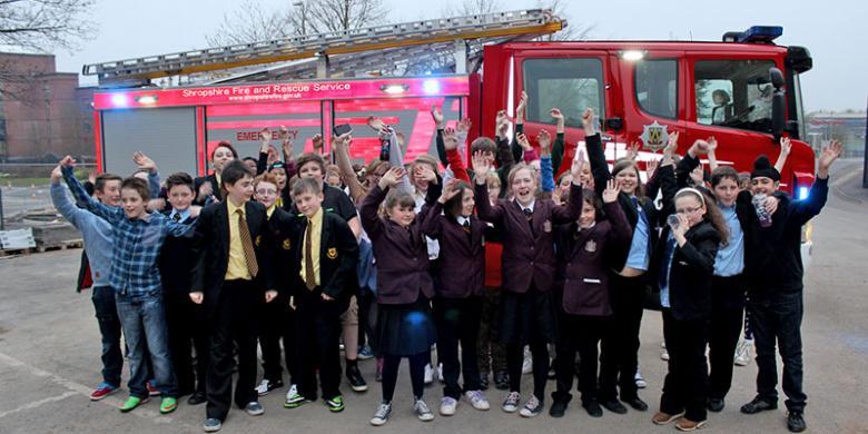School kids celebrate winning in front of a fire appliance