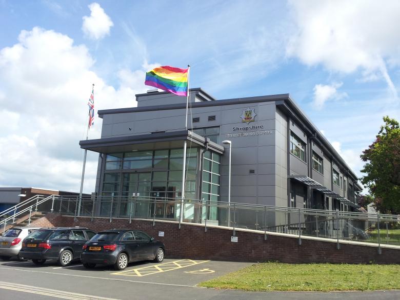 Rainbow flag flying against blue sky over Fire Service Headquarters