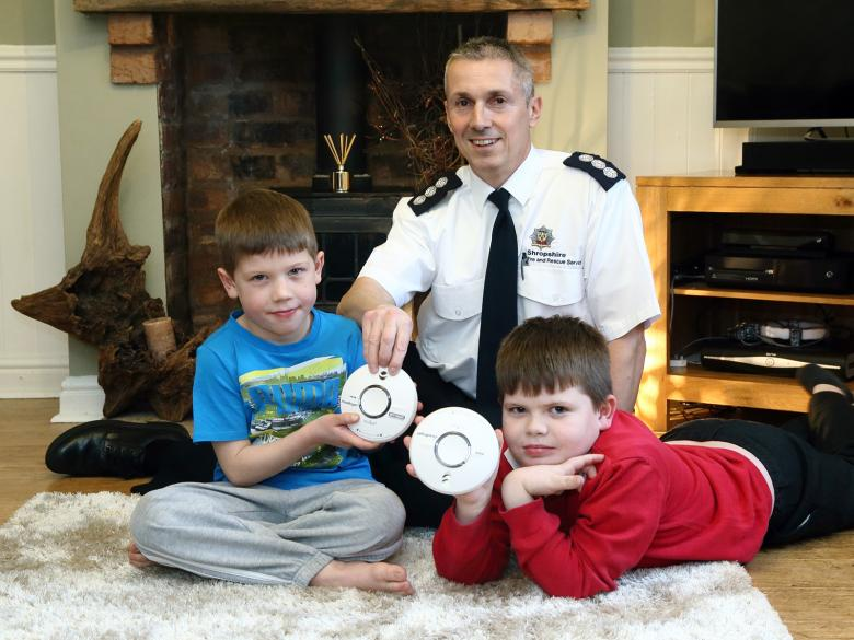 Ben (7) and Dillon (9), pictured with their own smoke alarms, get a visit from Guy Williams of Shropshire Fire and Rescue Service.